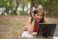Donna con il computer portatile in foresta Fotografie Stock