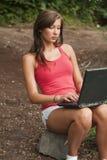 Donna con il computer portatile in foresta Fotografia Stock Libera da Diritti