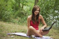 Donna con il computer portatile in foresta Immagine Stock Libera da Diritti