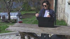 Donna con il computer portatile, lo smartphone ed il caffè