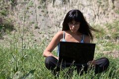 Donna con il computer portatile in natura Fotografie Stock Libere da Diritti
