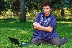 Donna con il computer portatile su prato inglese verde. Immagine Stock Libera da Diritti