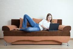 Donna con il computer portatile sul sofà Fotografie Stock