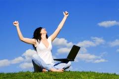 Donna con il computer portatile sull'erba verde immagine stock