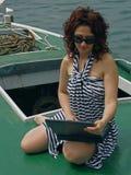 Donna con il computer portatile sulla barca fotografia stock