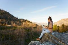 Donna con il computer portatile sulla montagna Fotografia Stock