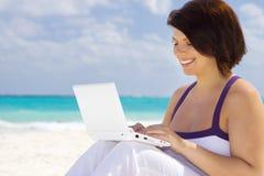 Donna con il computer portatile sulla spiaggia fotografie stock