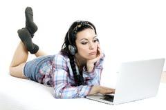 Donna con il computer portatile sullo strato bianco nel suo letto Immagine Stock