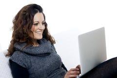 Donna con il computer portatile sullo strato bianco nel suo letto Immagini Stock