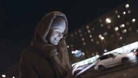 Donna con il cuscinetto di tocco che scrive sul suo modo nella notte archivi video