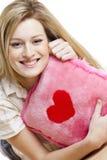 Donna con il cuscino con cuore Immagini Stock
