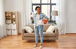 Donna con il detersivo di lavanderia e del canestro a casa fotografia stock