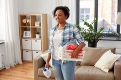 Donna con il detersivo di lavanderia e del canestro a casa immagini stock