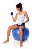 Donna con il Dumbbell che si siede sulla sfera di forma fisica Fotografia Stock
