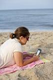 Donna con il E-lettore alla spiaggia Fotografia Stock