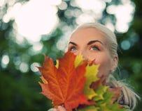 Donna con il foglio dorato di autunno fotografie stock libere da diritti