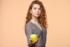Donna con il fondo del biege della mela Fotografia Stock