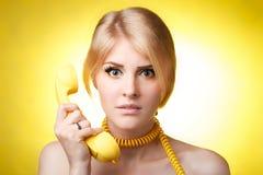 Donna con il fondo di giallo del telefono Immagini Stock Libere da Diritti