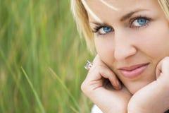 Donna con il fondo verde degli occhi azzurri dei capelli biondi fotografia stock libera da diritti