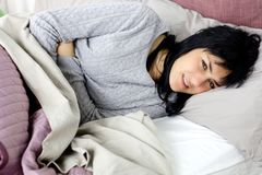 Donna con il forte dolore di stomaco di mestruazione che si trova a letto Fotografie Stock
