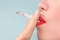 Donna con il fumo della sigaretta su un fondo leggero Fotografie Stock