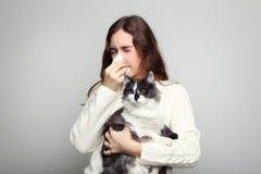 Donna con il gatto della tenuta di allergia fotografie stock