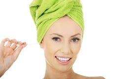 Donna con il germoglio del cotone in orecchio Fotografia Stock