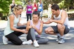 Donna con il ginocchio danneggiato durante la corsa in parco Fotografia Stock Libera da Diritti