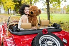 Donna con il giocattolo dell'orso in retro automobile Fotografia Stock