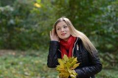 Donna con il gossip d'ascolto delle foglie di autunno a disposizione Fotografie Stock