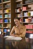 Donna con il libro allo scrittorio in biblioteca Fotografia Stock