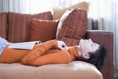 Donna con il libro aperto che si trova sul sofà Fotografia Stock