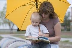 Donna con il libro di lettura del figlio sotto l'ombrello Fotografie Stock Libere da Diritti