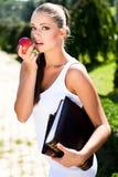 Donna con il libro e la mela Immagini Stock