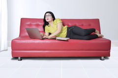 Donna con il libro ed il computer portatile sul sofà Fotografia Stock Libera da Diritti