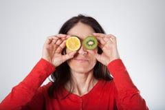 Donna con il limone ed il kiwi affettati su lei occhi Immagini Stock