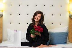 Donna con il mazzo di rose su un letto in hotel Fotografie Stock Libere da Diritti