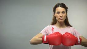 Donna con il nastro rosa in guantoni da pugile, combattenti contro il concetto del cancro al seno video d archivio