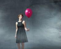 Donna con il pallone rosso a disposizione fotografia stock libera da diritti