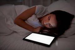 Donna con il pc della compressa che dorme a letto alla notte Fotografia Stock