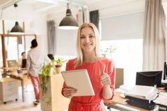 Donna con il pc della compressa che mostra i pollici su all'ufficio Immagine Stock Libera da Diritti