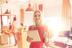 Donna con il pc della compressa che mostra i pollici su all'ufficio Fotografia Stock Libera da Diritti