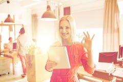 Donna con il pc della compressa che mostra segno giusto all'ufficio Immagine Stock Libera da Diritti