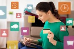 Donna con il pc della compressa e la carta di credito a casa Fotografia Stock