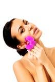 Donna con il petalo porpora dell'orchidea vicino al fronte Fotografia Stock Libera da Diritti