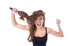 Donna con il pettine in capelli aggrovigliati gridi Isolato sul concetto bianco di salute dei capelli del fondo immagine stock