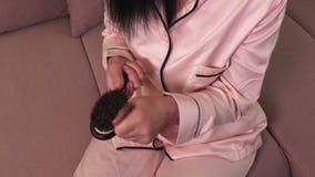 Donna con il pettine sul sofà