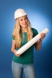 Donna con il piano del casco e della costruzione del costruttore felice di fare Fotografie Stock Libere da Diritti