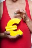 Donna con il piccolo risparmio ed euro piggyban a forma di Immagini Stock