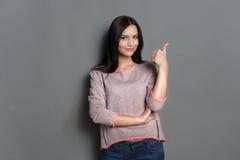 Donna con il pollice sul gesto su fondo grigio Immagini Stock Libere da Diritti
